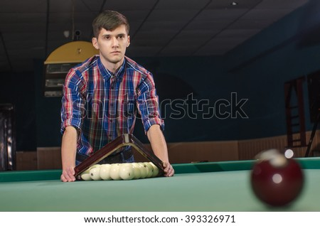 man in shirt prepare for start game of billiard with triangle - stock photo