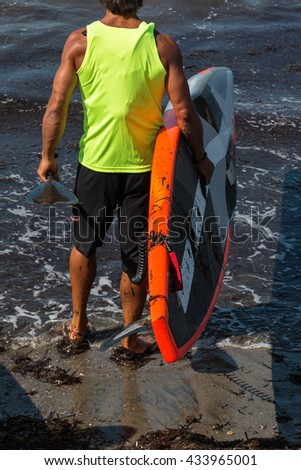 Man in Shoreline with His Board Underarm before Surfing  in the Sea - stock photo