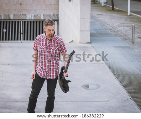 Man in short sleeve shirt holding electric guitar in the street