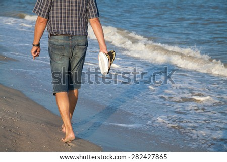 Man in shorts walking on sea beach summer evening - stock photo