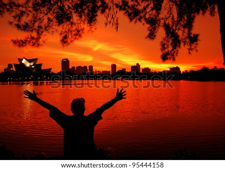 Man in silhouette with open arms freedom feeling over sunset background - stock photo