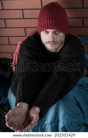 Man in sleeping bag with cupped hands asking for money