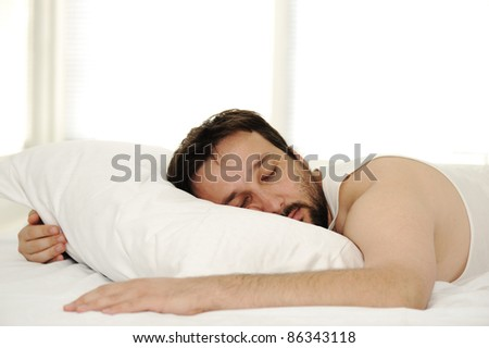 Man in sleeping bed, morning time - stock photo