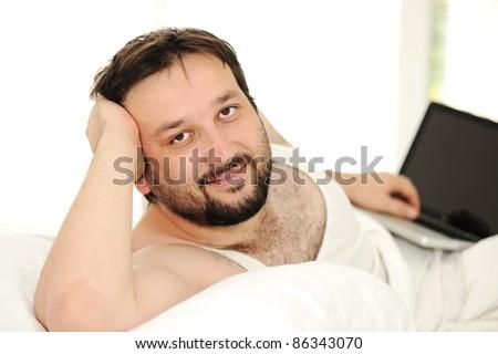 Man in sleeping bed using  laptop - stock photo