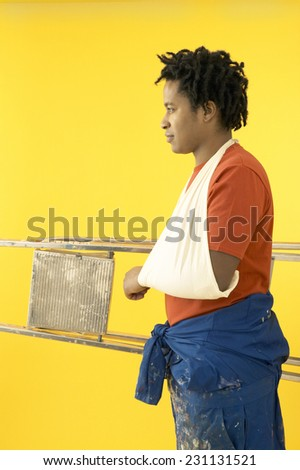 Man in Sling Carrying Ladder - stock photo