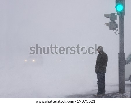 man in snowstorm stands on pedestrian crossing - stock photo