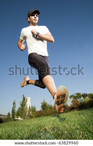 Man in sportswear jumping in a park - stock photo