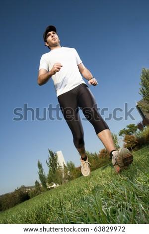 Man in sportswear running in a park - stock photo
