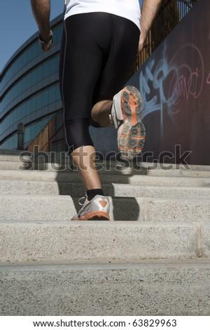 Man in sportswear running up a stairway - stock photo