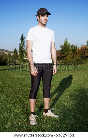 Man in sportswear standing in a park - stock photo