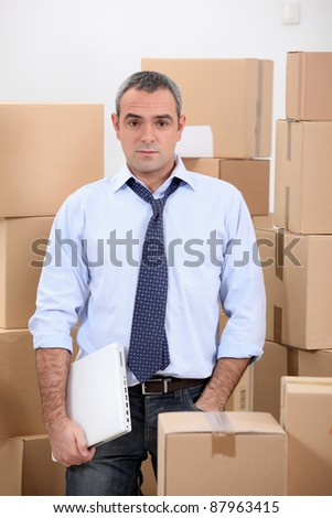 Man in storage depot surrounded by boxes - stock photo