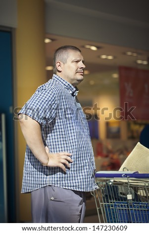 Man in store with trolley - stock photo