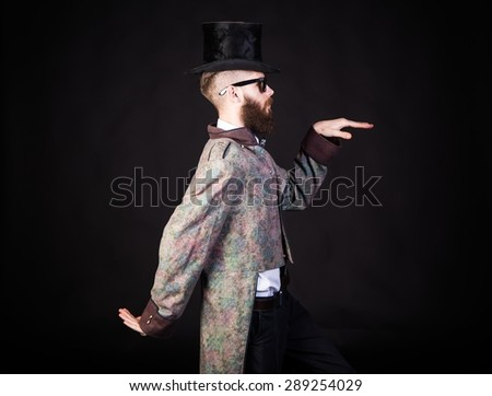 Man in strange outfit and sunglasses standing.