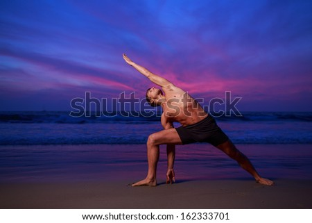Man in stretching yoga pose on ocean beach at dusk - stock photo