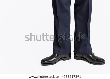 Man in Stylish Black Shiny Male Semi-Brogue Posing in Direct Position Against White. Horizontal Image Orientation - stock photo