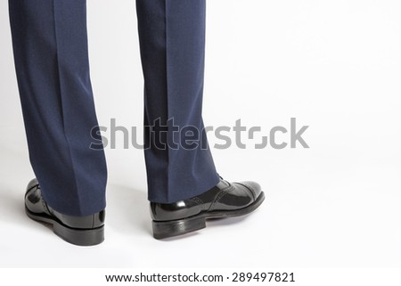 Man in Stylish Black Shiny Male Semi-Brogue Posing In Reversed Position Against White. Horizontal Image Orientation - stock photo