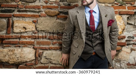 Man in suit agains the wall - stock photo