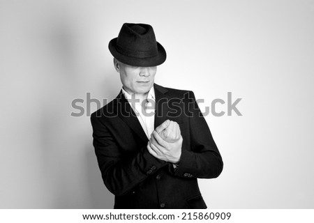 Man in suit and black hat at the age of forty-six years old looking at his hands on the background of a rough wall with texture - stock photo