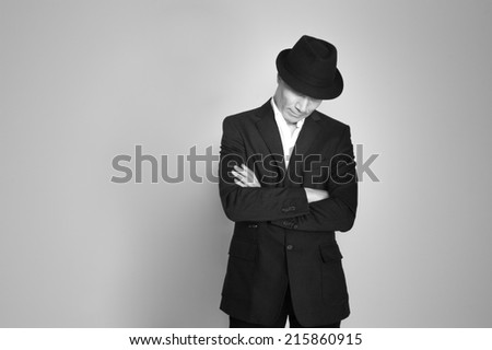 Man in suit and black hat at the age of forty-six years old looking down on the background of a rough wall with texture - stock photo