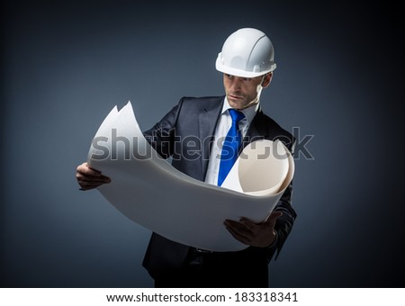 Man in suit and helmet with papers