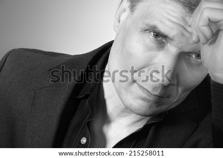 Man in suit at the age of forty-six years old  with hand to head support on the background of a rough wall with texture - stock photo