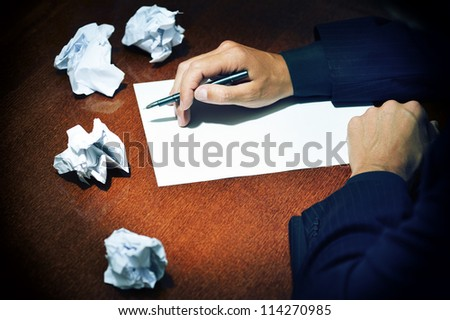 Man in suit at the table writing on a white sheet - stock photo