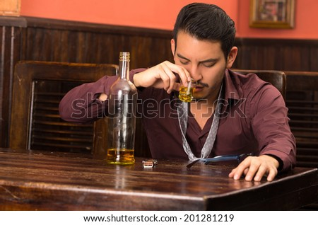 man in suit drinking alcohol shot with empty bottle