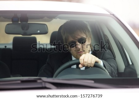 Man in suit driving a car - stock photo