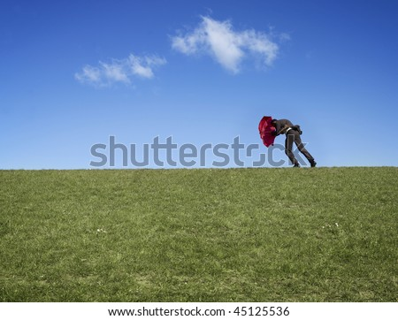 Man in suit fighting with umbrella against the wind in a field. - stock photo