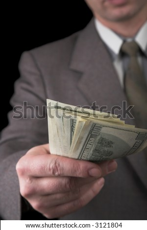 man in suit giving dollars isolated on black - stock photo