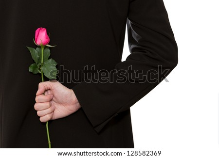man in suit holding a pink rose in his back - stock photo