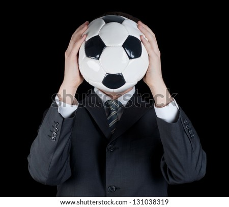 man in suit holding a soccer ball in front of his face - stock photo