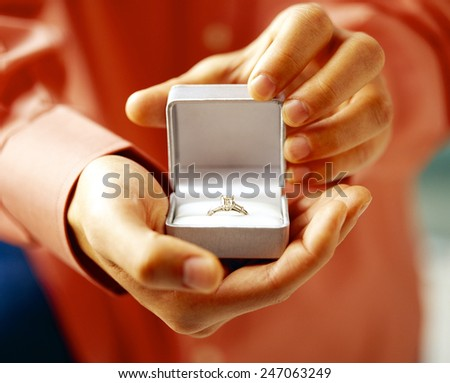Man in suit holding engagement ring - stock photo