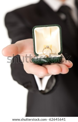 Man in suit holding engagement ring on white isolated background - stock photo
