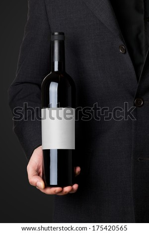 Man in suit holding red wine bottle isolated on black background - stock photo