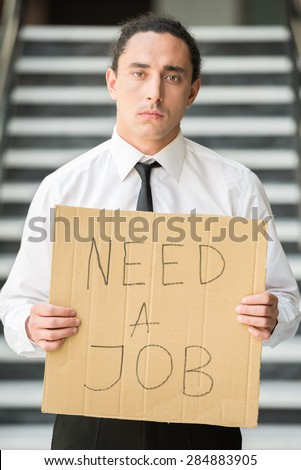 Man in suit holding sign in hands. Unemployed man looking for job. - stock photo