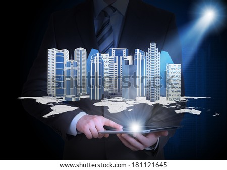 Man in suit holding tablet pc and city of skyscrapers in the hand. Spotlight shines skyscrapers - stock photo