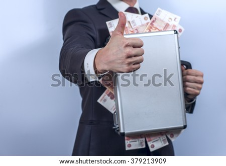 Man in suit holds metal briefcase full of russian banknotes and shows thumbs up gesture. Conception of safe storage and protection of cash. Financial theme. Horizontal view. - stock photo