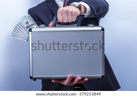 Man in suit holds metal briefcase with dollars on grey background.  Conception of safe storage and protection of cash. Financial theme. Horizontal view. - stock photo