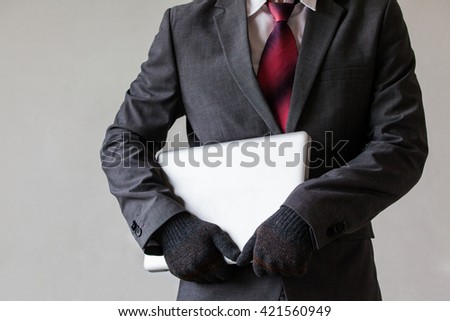 Man in suit is stealing a laptop - data or information, computer stealing concept - stock photo