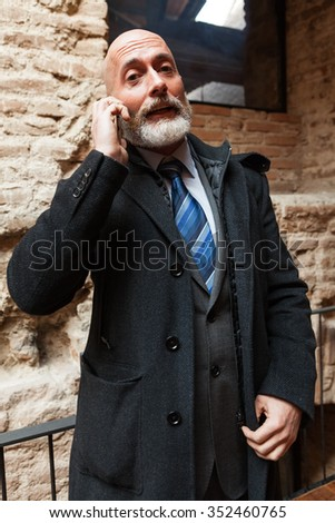 Man in suit jacket handsome , modern and stylish tie is consulting information and talking through his mobile - stock photo