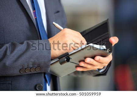 Man in suit keeping notes in his organizer