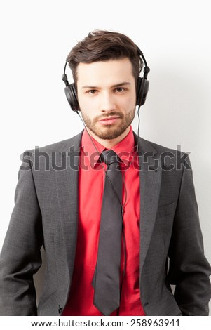 Man in suit listening to music with headphones