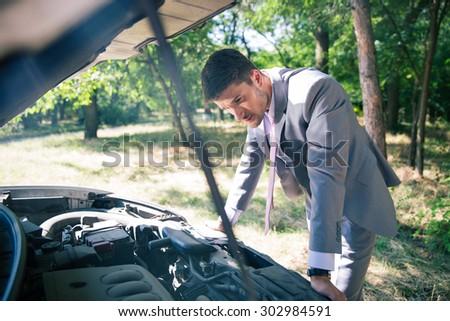Man in suit looking under the hood of breakdown car - stock photo