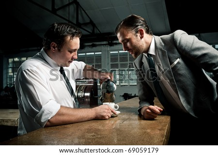 Man in suit looks at how the barista pours the next cup of coffee - stock photo