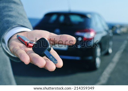 man in suit offering a car key to the observer, with a car in the background - stock photo