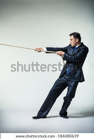Man in suit pulling a rope