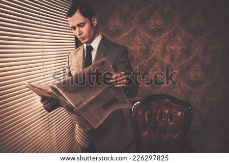 Man in suit reading newspaper near window - stock photo