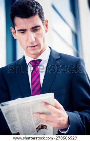 Man in suit reading newspaper outdoors in front of office building