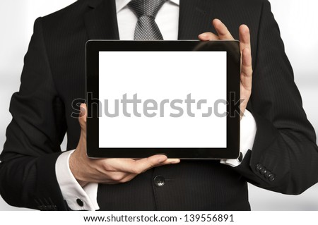 Man in suit, shirt and tie holding a tablet computer with blank display - stock photo